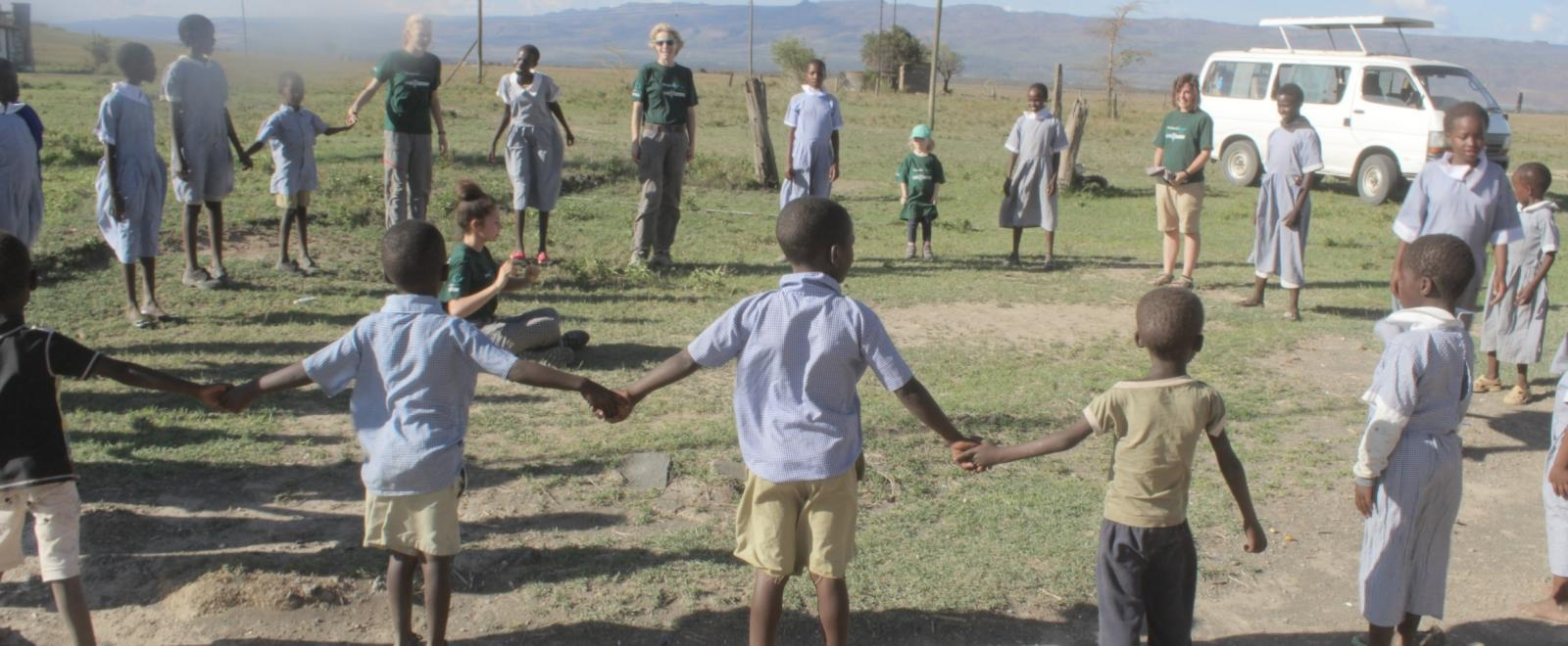 A family volunteering abroad together help run a fun educational activity outside for Kenyan school children.